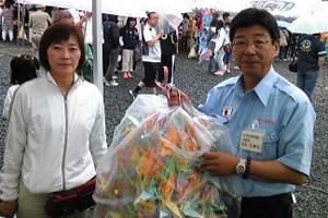 「福興市」で、酒田の小学生たちが集めた文房具と千羽鶴を南三陸町の佐藤仁町長に手渡す(2011年6月26日)
