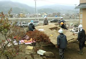 壊滅的な津波被害を受けた気仙沼市鹿折地区。居間に突っ込んだ別のお宅の屋根をどかすチーム気仙沼のみんな