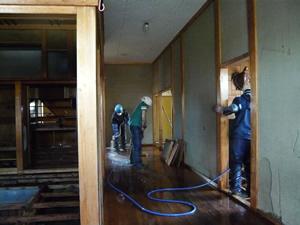 同じく気仙沼市鹿折地区。泥上げをした後の床や壁をホース水で洗い流しているところ。このあと、乾かして、石灰や消毒液をまいて、滅菌して、床板を戻す