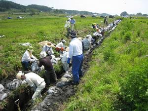 寒河江市柴橋地区の役員の方たちも参加し、猛暑の中、田んぼの用水路の泥あげ作業(2012年7月29日・陸前高田市)